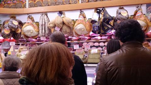 Clientes na fila da Salumeria Simoni. Vale apreciar a paisagem de salames e prosciuttos atrás do balcão
