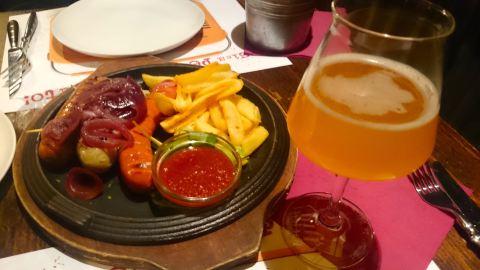 Porção de salsichas  mistas com cebola roxa caramelizada e fritas, no Pub da cervejaria Baladin