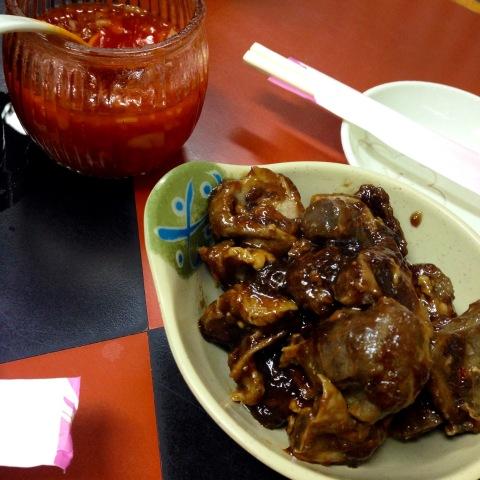 Porção de moela cozida em molho de shoyu, gengibre e cebola da Dona Líria, no Bar Kintaro. Molho de pimenta tem cebola picada.