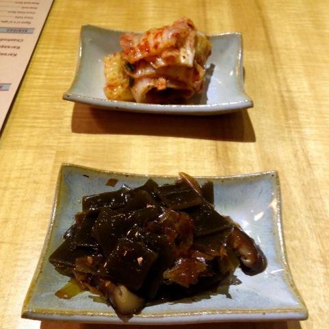Para beliscar: kimchi (ao fundo) e alga curtida com peixe (tsukudani).