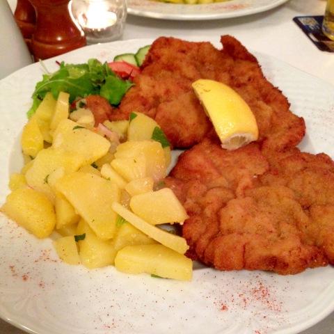 Prato-banquete com schnitzel de lombo de porco e salada de batatas cozidas.